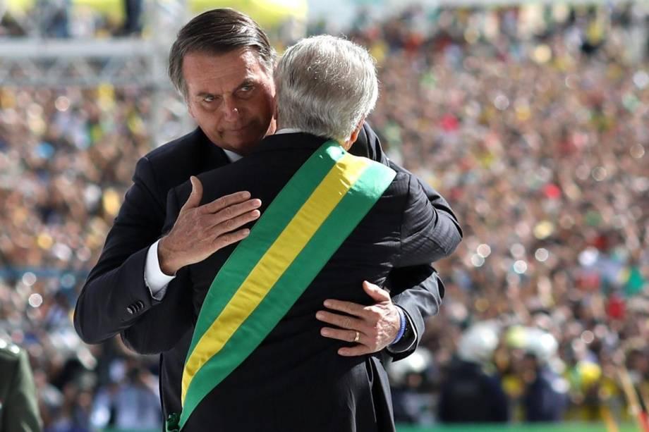 O presidente Jair Bolsonaro recebe a faixa presidencial das mãos do antecessor, Michel Temer, em cerimônia no Palácio do Planalto, em Brasília - 01/01/2019