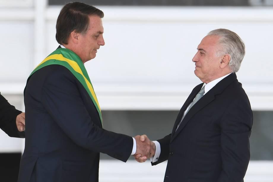 Presidente Jair Bolsonaro recebe a faixa presidencial do ex-presidente Michel Temer após subir a rampa do Palácio do Planalto, em Brasília - 01/01/2019