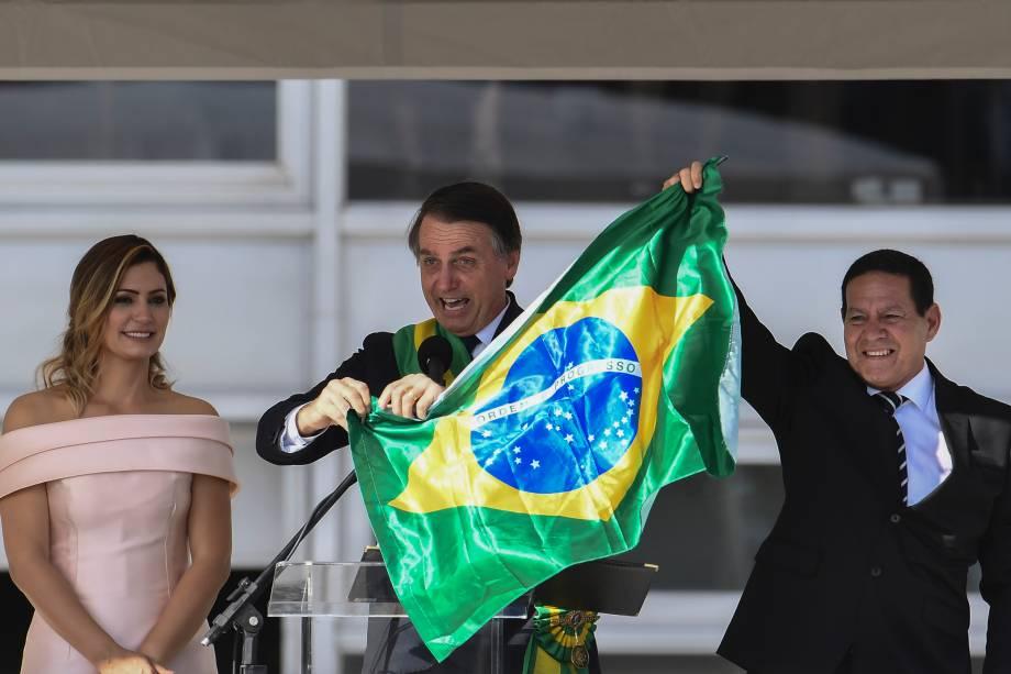 Presidente Jair Bolsonaro o vice-presidente Hamilton Mourão exibem uma bandeira nacional durante discurso no Palácio do Planalto em Brasília - 01/01/2018