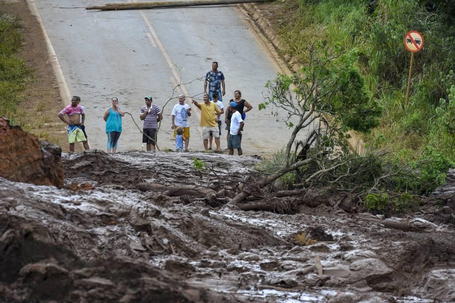 Moradores observam o mar de lama no trecho de uma estrada após o rompimento da barragem da mina do Córrego do Feijão em Brumadinho (MG)