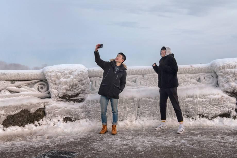Visitantes tiram uma selfie nas Cataratas do Niágara, que teve boa parte das estruturas e quedas d'água congeladas devido às temperaturas abaixo de zero - 23/01/2019