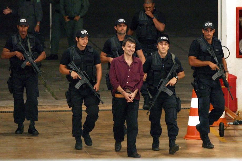 O ex-ativista de extrema esquerda italiano Cesare Battisti, 52, é escoltado por policiais da Polícia Federal ao chegar em Brasília (DF). Battisti foi um dos chefes da organização de extrema esquerda Proletários Armados pelo Comunismo. Os assassinatos pelos quais foi condenado ocorreram em 1978 e 1979. Ele foi preso no Rio de Janeiro, onde estava desde 2004 - 19/03/2007