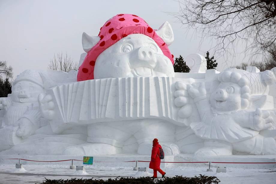 Visitante passa por escultura de porco feita de neve e gelo no Festival Internacional de Esculturas de Gelo e Neve de Harbin. A escultura representa o animal do próximo Ano Novo Lunar - 04/01/2019
