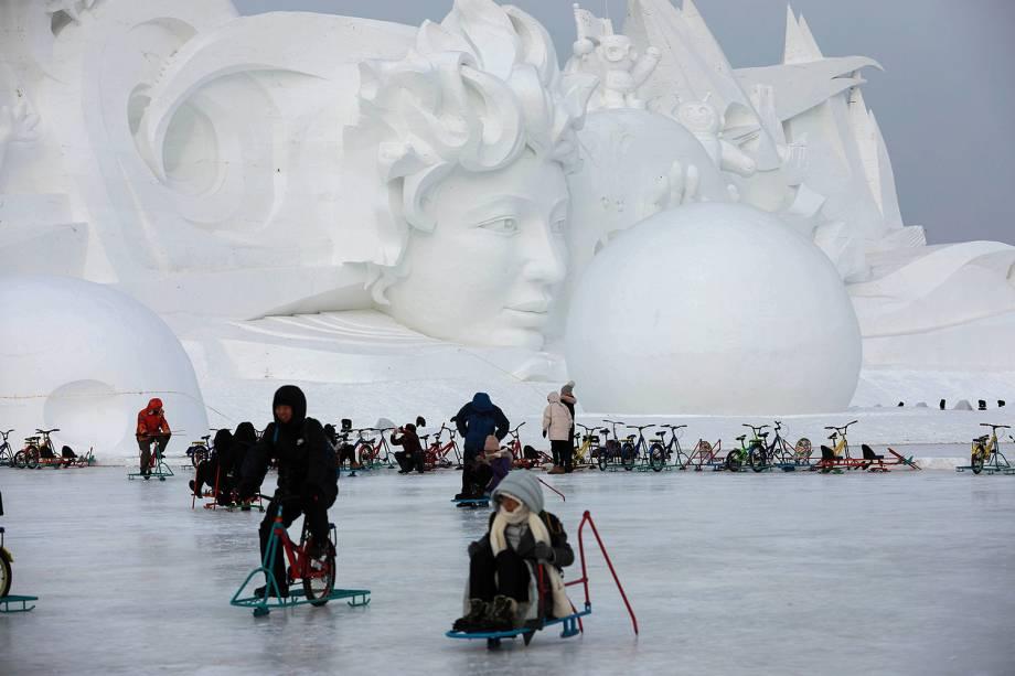 Pessoas brincam no gelo em frente a uma escultura de neve parte do Festival Internacional de Esculturas de Gelo e Neve de Harbin, província de Heilongjiang, China - 04/01/2019