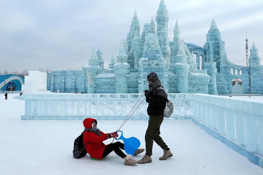 Visitantes brincam em frente a esculturas de gelo no Festival Internacional de Esculturas de Gelo e Neve de Harbin, província de Heilongjiang, China - 04/01/2019