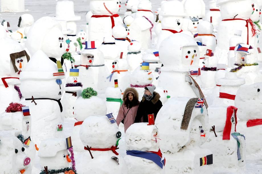 Casal caminha entre bonecos de neve que fazem parte de exibição no Festival Internacional de Esculturas de Gelo e Neve de Harbin, província de Heilongjiang, China - 04/01/2019
