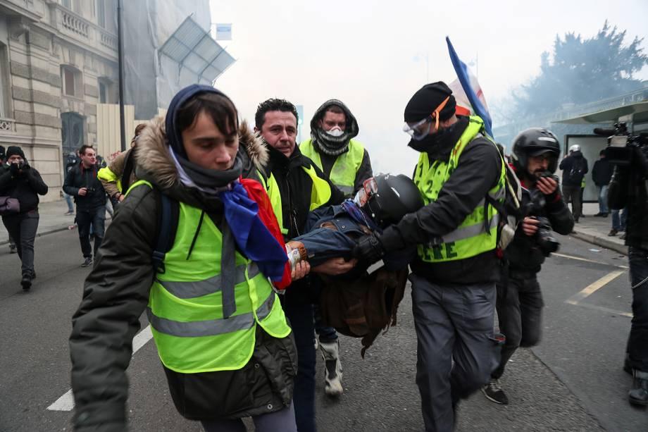 Maniestantes com coletes amarelos carregam fotógrafo ferido durante protestos contra o governo em Paris, capital da França - 05/01/2019