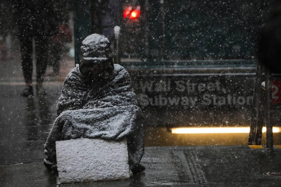 Morador de rua é coberto de neve enquanto fica sentado ao lado da estação Wall Street do metrô de Nova York - 30/01/2019