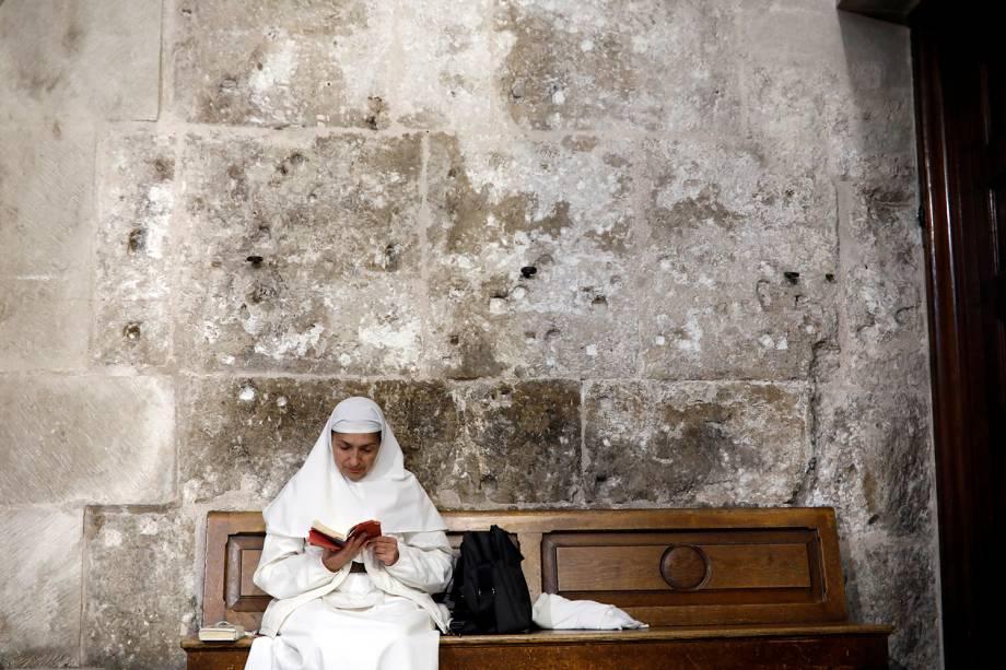 Freira lê sentada em banco dentro da Igreja do Santo Sepulcro na Cidade Velha de Jerusalém - 17/11/2018