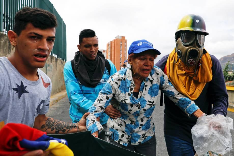 Manifestantes se protegem de bombas de gás lacrimogêneo lançadas por policiais, durante marcha contra o presidente venezuelano Nicolás Maduro, em Caracas - 23/01/2019