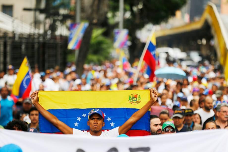 Manifestante carrega bandeira da Venezuela durante marcha contra o presidente Nicolás Maduro, em Caracas - 23/01/2019