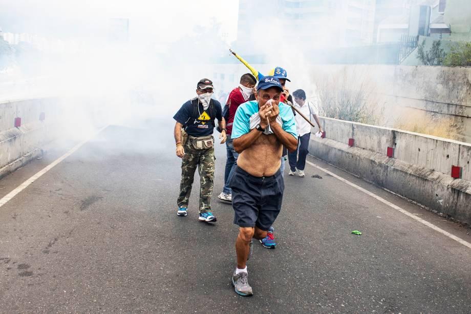 Manifestantes se protegem de bombas de gás lacrimogêneo lançadas pela polícia, durante marcha contra o presidente venezuelano Nicolás Maduro - 23/01/2019