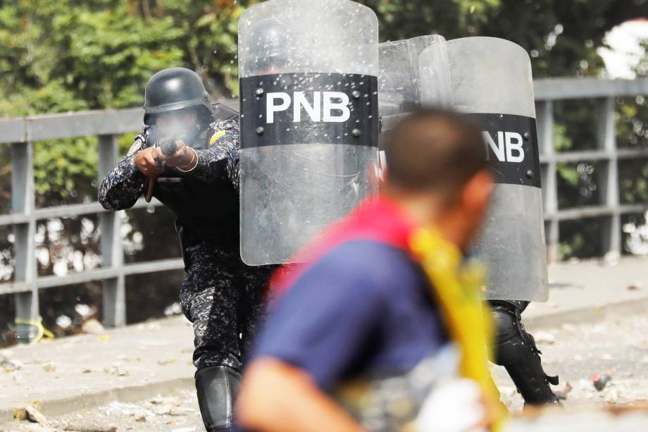 Policial atira contra manifestante durante marcha contra o governo do presidente venezuelano Nicolás Maduro, em Caracas - 23/01/2019