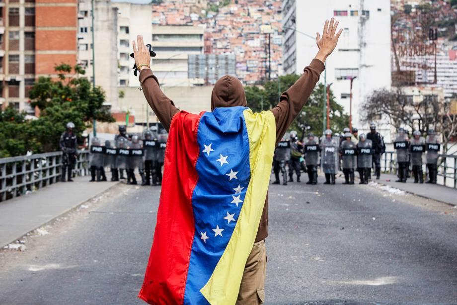 Homem com bandeira da Venezuela levanta os braços na frente de policiais durante marcha contra o presidente Nicolás Maduro - 23/01/2019