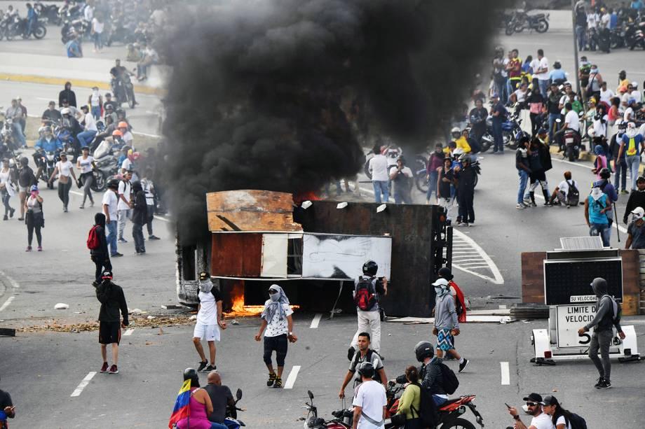 Veículo é incendiado durante marcha contra o governo do presidente venezuelano Nicolás Maduro, em Caracas - 23/01/2019