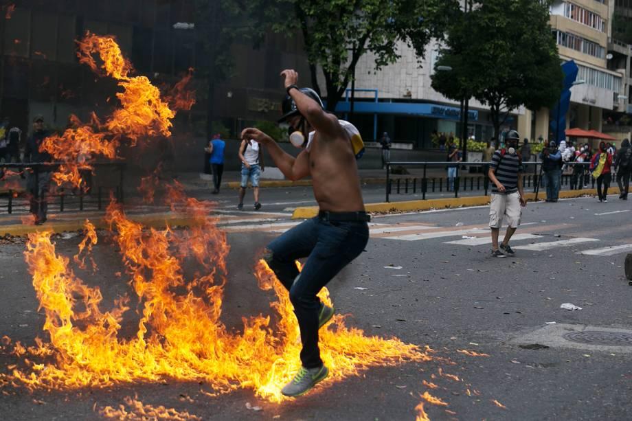 Manifestante salta sobre fogo durante protesto contra o governo do presidente venezuelano Nicolás Maduro, em Caracas - 23/01/2019