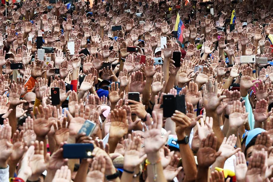Manifestantes erguem as mãos durante juramento solene de Juan Guaidó, que se declarou presidente interino da Venezuela, durante marcha contra o governo de Nicolás Maduro, em Caracas - 23/01/2019