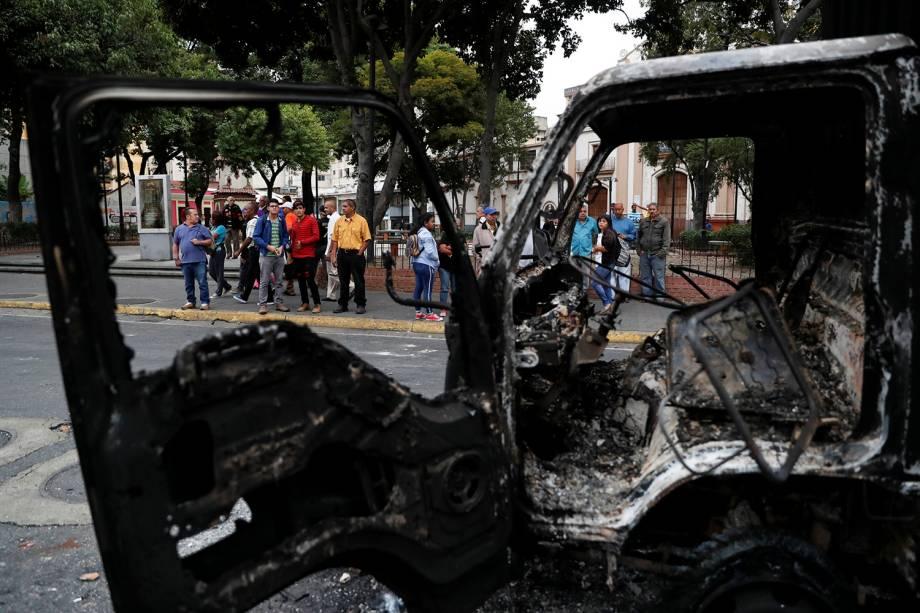 Pessoas observam um caminhão que foi queimado durante os protestos contra o governo de Nicolas Maduro em Caracas, Venezuela - 24/01/2019