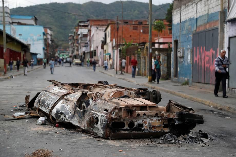 Um carro queimado durante os protestos contra o governo de Nicolas Maduro em Caracas, na Venezuela, é visto no meio da rua - 24/01/2019