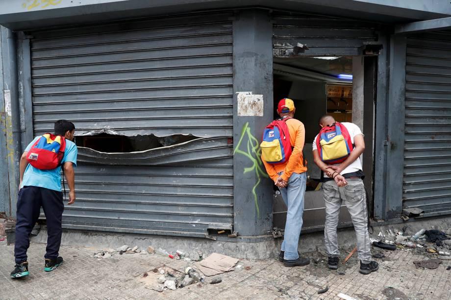 Homens olham dentro de uma loja de liquor saqueada após os protestos contra o governo de Nicolas Maduro em Caracas, na Venezuela - 24/01/2019