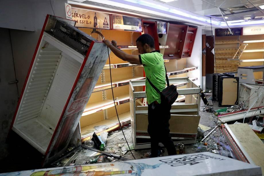 Trabalhador levanta uma geladeira dentro de uma loja de liquor saqueada após os protestos contra o governo de Nicolas Maduro em Caracas, na Venezuela - 24/01/2019