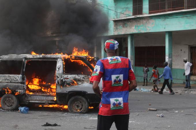 A man dressed in national colours stands near a burning car, during anti-government protests in Port-au-Prince
