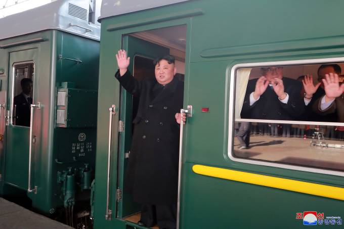 North Korean leader Kim Jong Un waves from a train as he departs for a summit in Hanoi