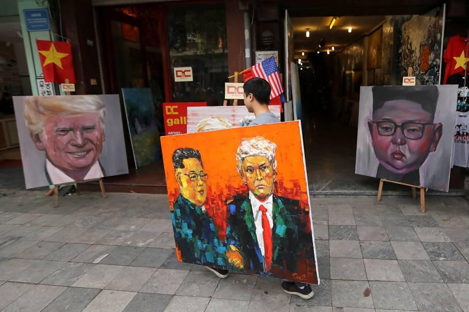 Um homem que carrega uma pintura de Donald Trump e Kim Jong-un passa em frente a outras duas pinturas dos líderes de EUA e Coréia do Norte, antes da cúpula que acontecerá em Hanói, no Vietnã - 27/02/2019