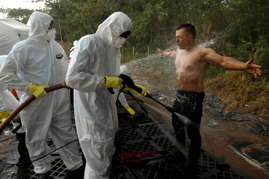 Membro da equipe de resgate recebe jatos de água para remoção de lama proveniente do rompimento de barragem em Brumadinho - 13/02/2019