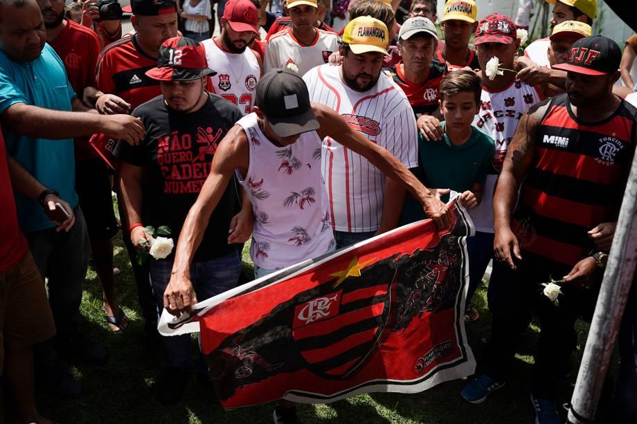 Um torcedor segura uma bandeira do Flamengo para homenagear as vítimas do incêndio no centro de treinamento Ninho do Urubu, no Rio de Janeiro - 08/02/2019