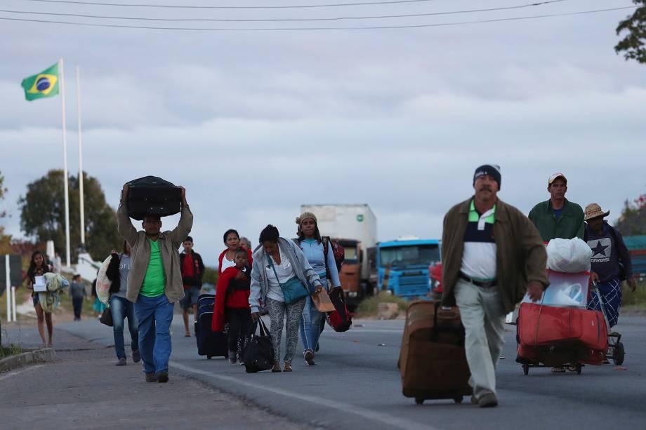 Pessoas carregam malas durante a travessia da Venezuela para o Brasil, em Pacaraima, no estado de Roraima - 22/02/2019