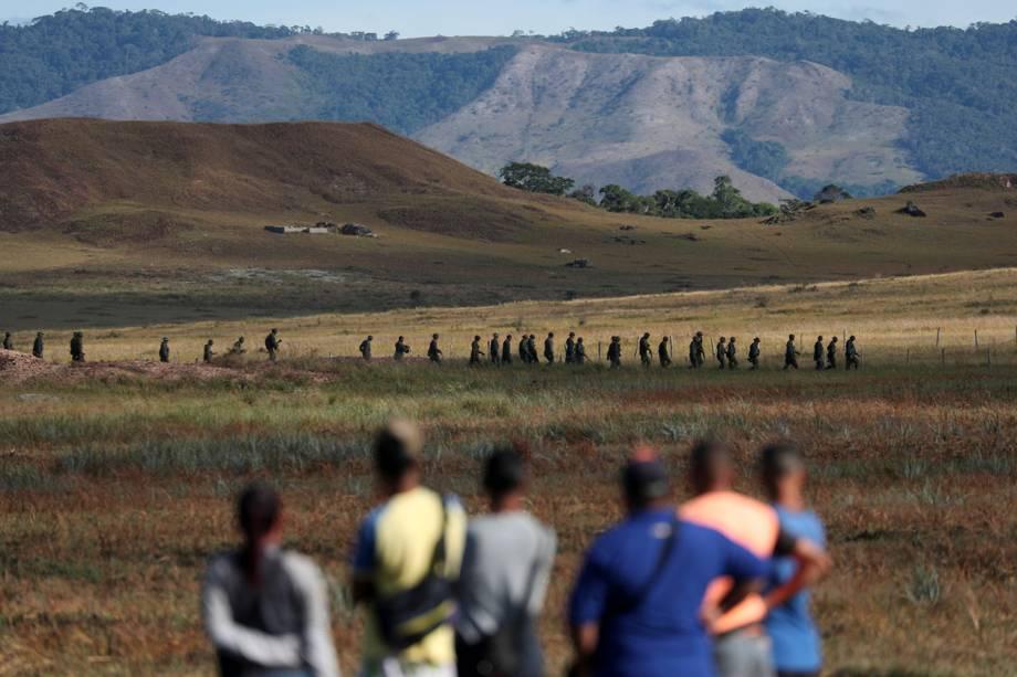 Pessoas observam militares venezuelanos enquanto andam próximos à fronteira entre Brasil e Venezuela no município de Pacaraima, Roraima - 22/02/2019