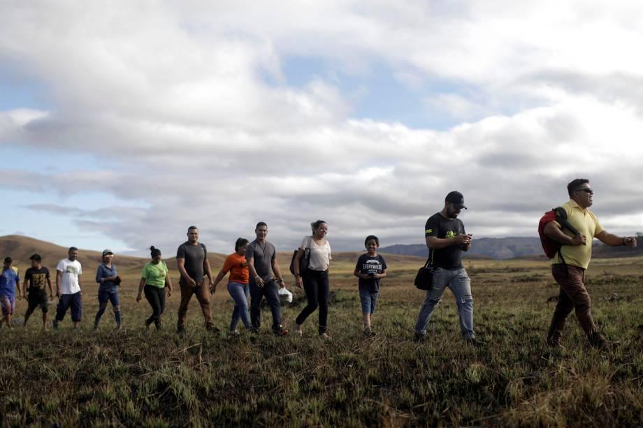 Pessoas andando em fila tentam atravessar a fronteira fechada entre Brasil e Venezuela em Pacaraima, estado de Roraima - 22/02/2019