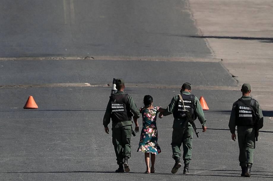 Mulher é carregada por militares venezuelanos na fronteira entre a Venezuela e o Brasil em Pacaraima, estado de Roraima - 22/02/2019