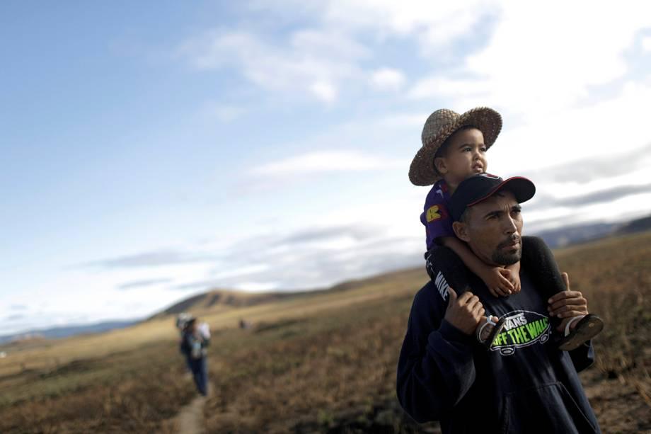 Um homem com o filho nos ombros tenta atravessar a fronteira fechada entre Brasil e Venezuela em Pacaraima, estado de Roraima - 22/02/2019