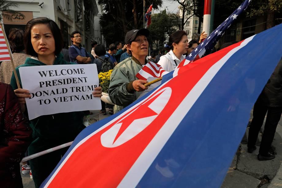 Pessoas seguram bandeiras e cartazes de boas vindas ao presidente dos EUA Donald Trump diante do hotel Metropole, onde ocorrerá umn jantar com o líder norte coreano Kim Jong-un, em Hanói, no Vietnã - 27/02/2019