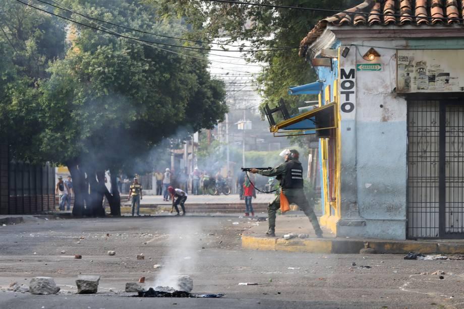 Membro da força de segurança da Venezuela aponta sua espingarda durante confronto com os manifestantes em Ureña, Venezuela - 23/02/2019