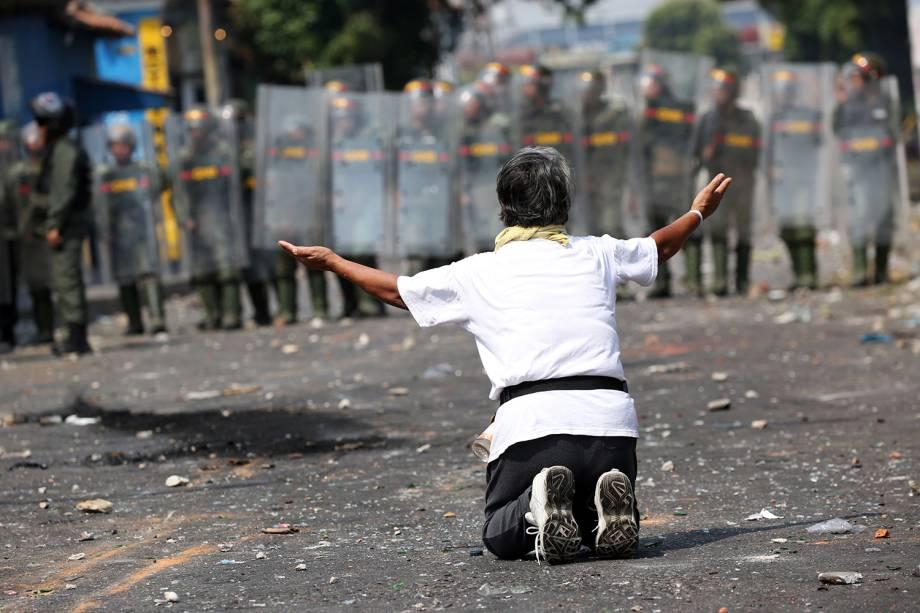 Manifestante ajoelha em frente a força de segurança em Ureña, Venezuela - 23/02/2019