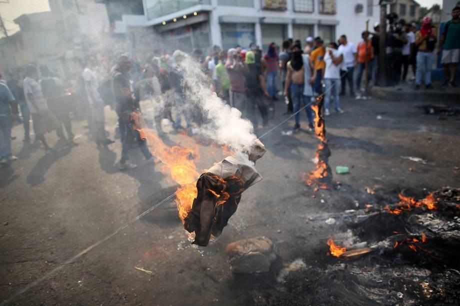 Manifestantes queimam uniforme da milícia durante confronto com as forças de segurança em Ureña, Venezuela - 23/02/2019