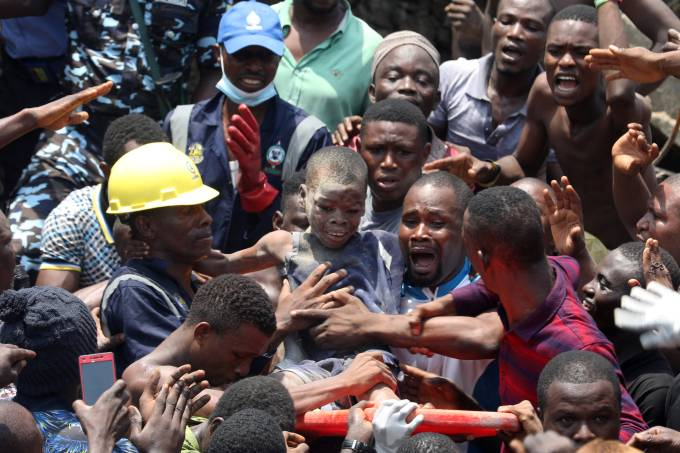 Men carry a boy who was rescued at the site of a collapsed building containing a school in Nigeria's commercial capital of Lagos