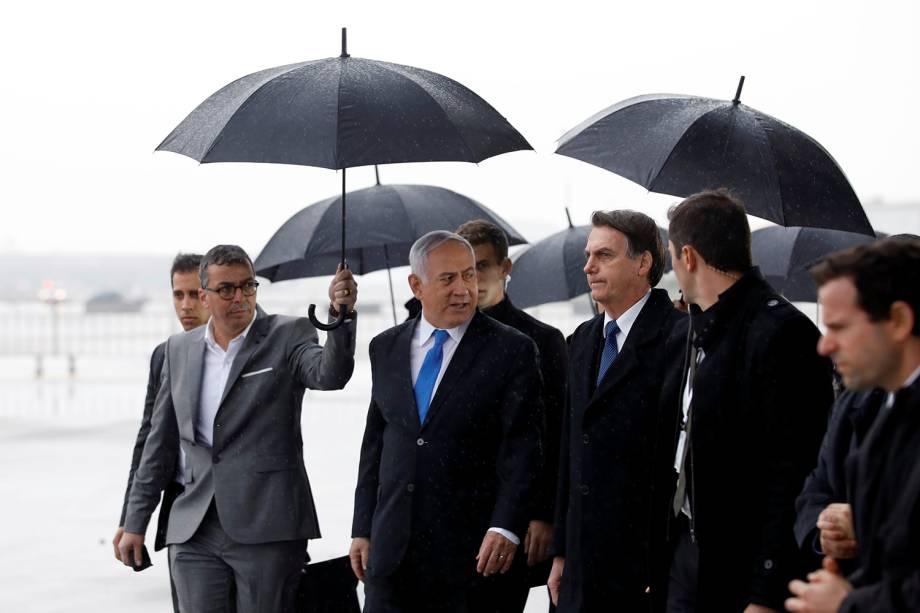 A comitiva do primeiro-ministro israelense, Benjamin Netanyahu, segura guarda-chuvas enquanto caminham com o presidente brasileiro Jair Bolsonaro durante uma cerimônia de boas-vindas em sua chegada à Israel - 31/03/2019