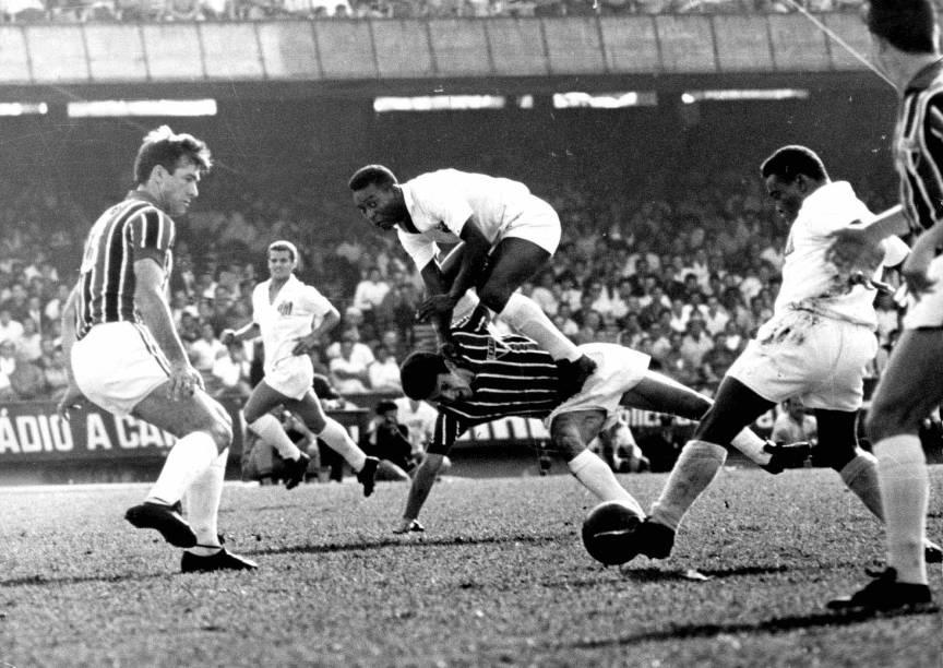 11 de outubro de 1964 - Em jogo contra o São Paulo, Pelé salta sobre o zagueiro Roberto Dias à espera do passe de Coutinho (com a bola), que é observado por Bellini, no Estádio do Morumbi, pelo Campeonato Paulista de Futebol