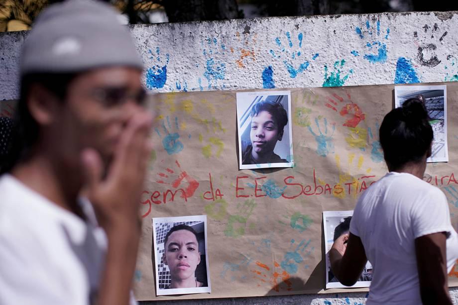 Um mural em homenagem às vítimas do massacre na Escola Raul Brasil, em Suzano, é visto atrás de alunos durante a reabertura da escola - 19/03/2019