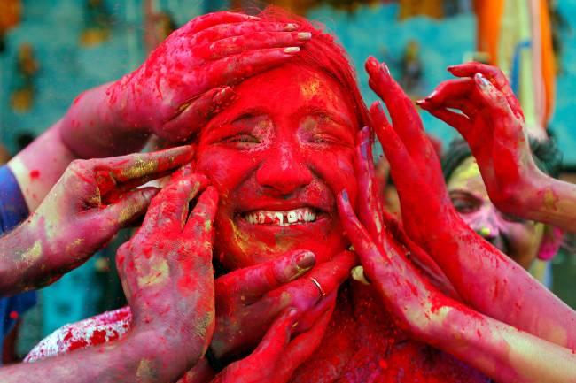 Mulher têm seu rosto colorido com pó vermelho durante o festival Holi, em Calcutá – 21/03/2019