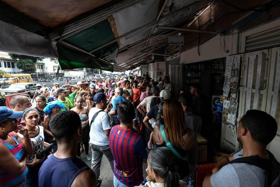 Pessoas fazem fila para comprar comida no bairro de Petare em Caracas durante uma queda de energia maciça. Domingo é o terceiro dia em que os venezuelanos permanecem sem comunicação, eletricidade ou água - 10/03/2019