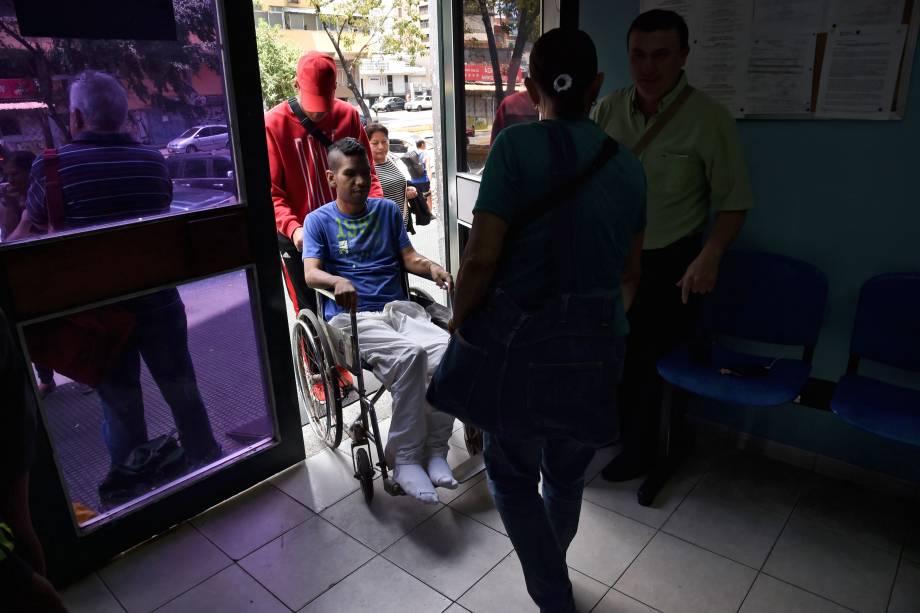 Parentes empurram um homem em uma cadeira de rodas em um clínica de tratamento para insuficiência renal estatal em Caracas, na Venezuela no terceiro do apagão que afeta praticamente toda a Venezuela - 10/03/2019