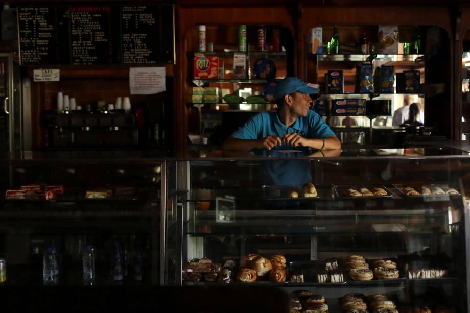 Trabalhador fica dentro de uma padaria às escuras durante  apagão em curso em Caracas, Venezuela - 10/03/2019