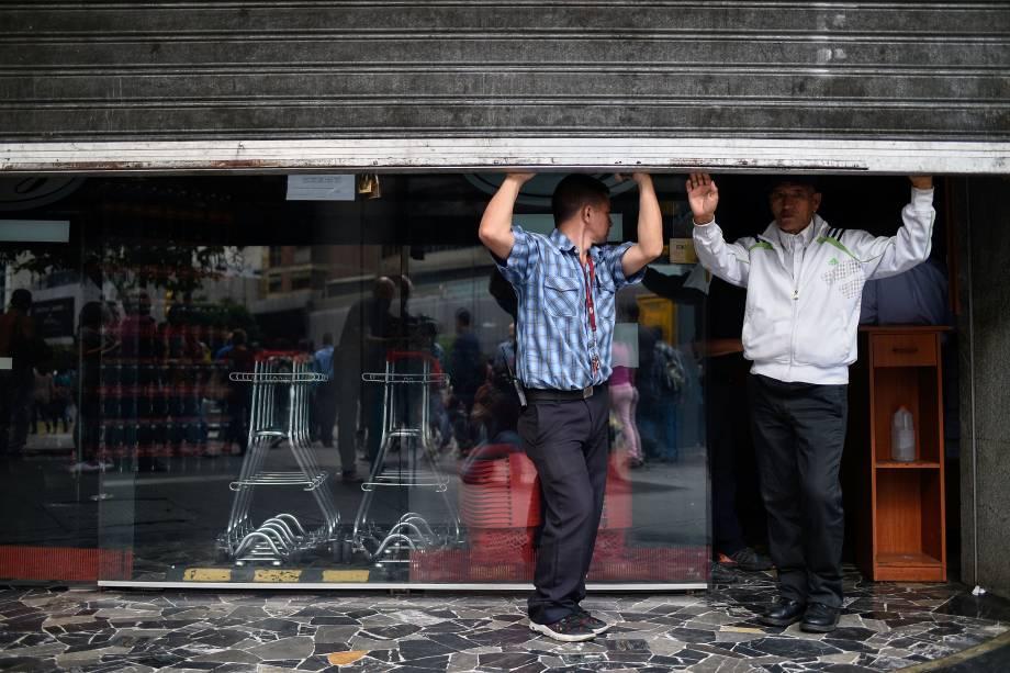 Empregados fecham as portas de um supermercado, durante um corte de energia em Caracas, na Venezuela - 07/03/2019