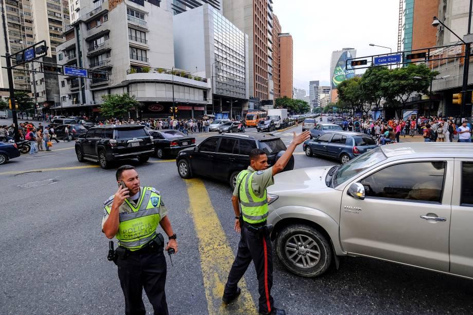 Policiais direcionam o tráfego em uma interseção durante um corte de energia em Caracas, na Venezuela - 07/03/2019