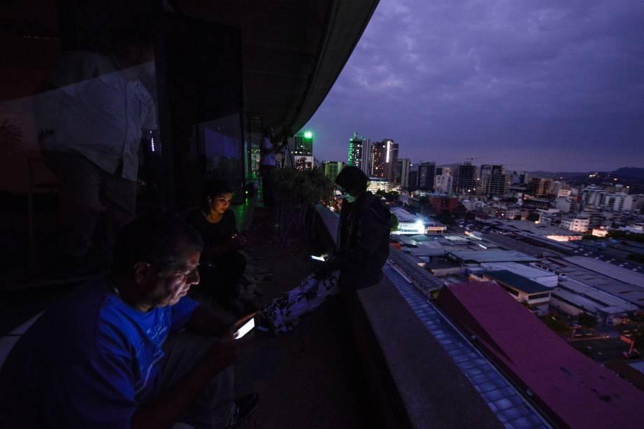 Jornalistas usam seus smartphones, durante corte de energia em Caracas, na Venezuela - 07/03/2019